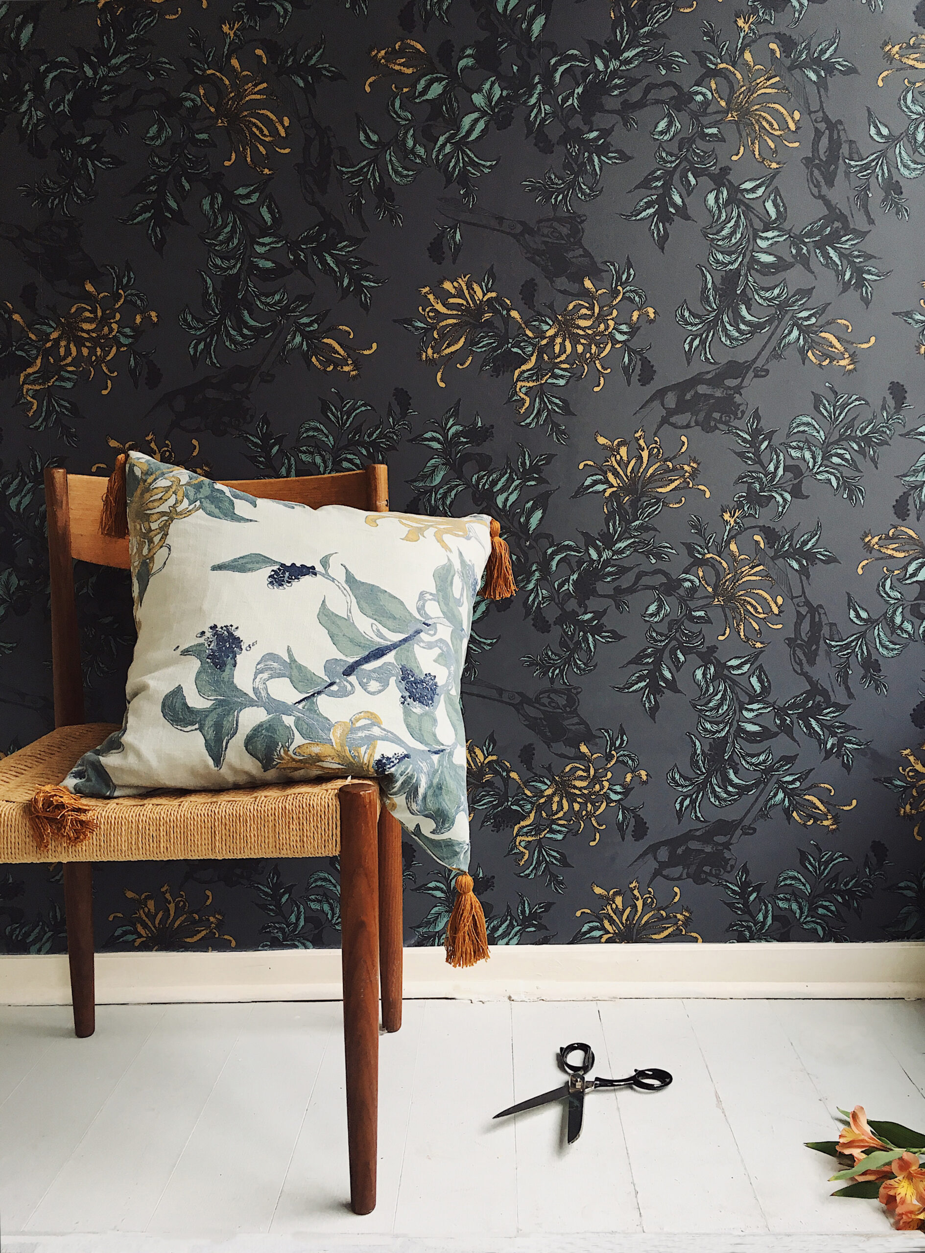 snip floral wallpaper and chair with pillow